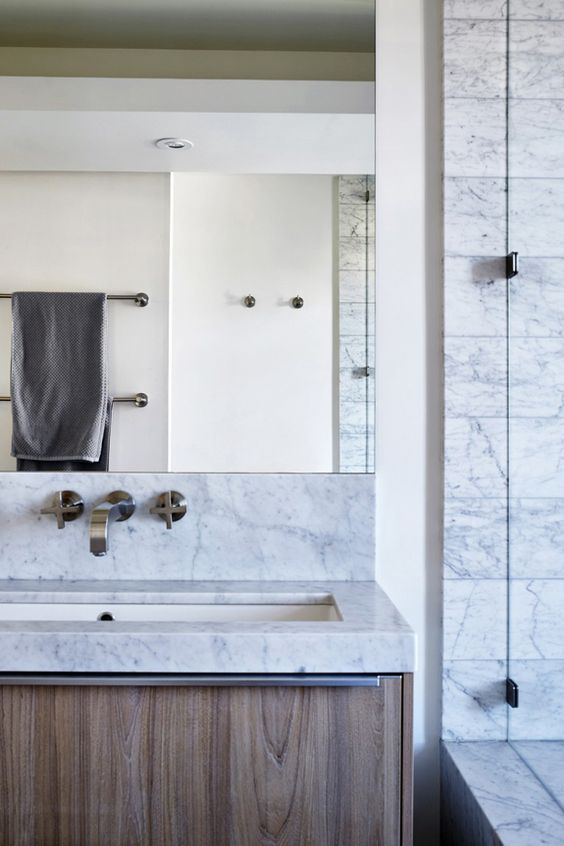 This San Francisco penthouse by SVZ Interior Design has a modern sophistication that has me wanting to touch all the things. The marble at this bathroom counter, turning up in line with the mirror, is just gorgeous. #ThisOldHouse inspiration via www.L-2-Design.com